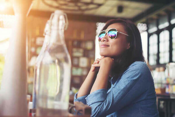 Thoughtful young hipster woman with glasses sitting at table at cafe.