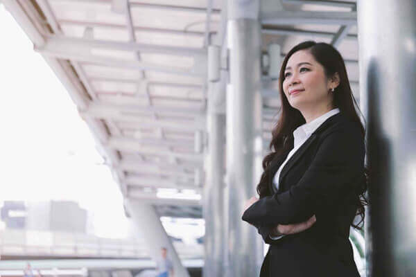 Successful asian senior businesswoman leader standing over modern office background