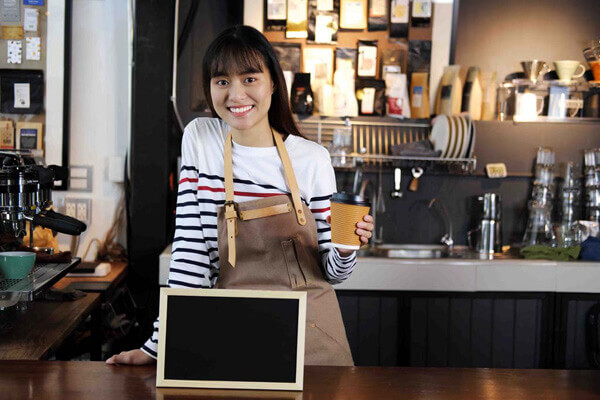 Portrait of smiling asian barista holding cup of coffee with blank chalkboard menu at counter in coffee shop. Cafe restaurant service, food and drink industry concept.