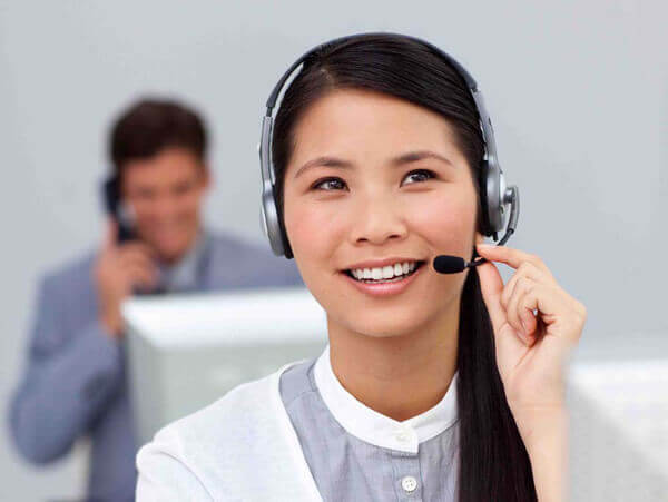 Young asian businesswoman with headset on at her desk in the office